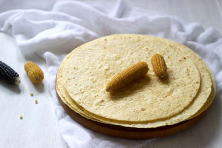A stack of round corn tortillas on a wooden board and corncobs. Selective focus.
