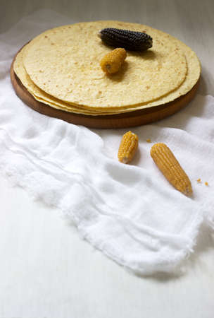A stack of round corn tortillas on a wooden board and corncobs. Selective focus. Stok Fotoğraf - 124906113