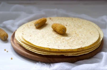 A stack of round corn tortillas on a wooden board and corncobs. Selective focus. Stok Fotoğraf - 124906160