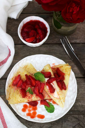 Thin pancakes with cream filling and strawberry sauce on a wooden table. Rustic style, selective focus. Banque d'images - 124906163