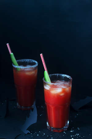Cocktail Bloody Mary or Virgin Mary with a cucumber on a dark background with bats. Halloween concept.