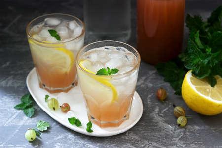 Limonade à la groseille avec menthe et glace, une bouteille d'eau et une bouteille de sirop de groseille sur une surface en béton. Mise au point sélective.