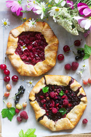 Galette pies with juicy berry filling, berries and wild flowers on a wooden background. Rustic style.