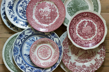Vintage porcelain plates in different sizes and colors on a wooden background. Rustic style.