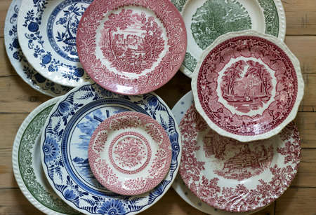Vintage porcelain plates in different sizes and colors on a wooden background. Rustic style, selective focus.