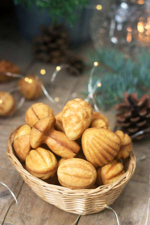 Homemade shortbread cookies in various shapes, filled with caramel on the background of fir branches and garlands.