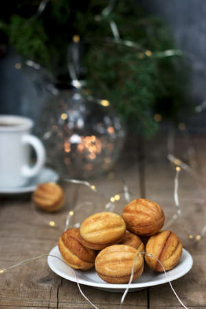 Homemade shortbread cookies in the shape of nuts on the background of a cup of coffee, fir branches and garlands. Rustic style, selective focus. Stok Fotoğraf