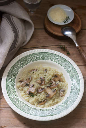 Traditional italian dish risotto with champignons in a light plate on a wooden table. Rustic style. Фото со стока