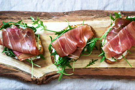 Traditional italian appetizer bruschetta of toasted bread with cottage cheese, arugula and prosciutto. Selective focus.