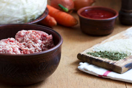 Ingredients for the preparation of a traditional Moldavian or Romanian dish of stuffed cabbage. Minced meat, sauerkraut, vegetables, rice and spices. Selective focus. Zdjęcie Seryjne