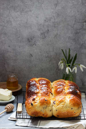 Traditional hot cross buns with honey and butter on a concrete background.