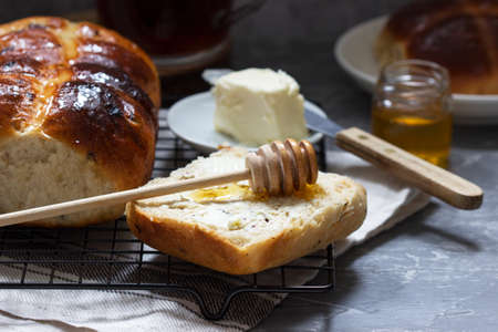 Traditional hot cross buns with honey and butter on a concrete background. Selective focus. Stockfoto