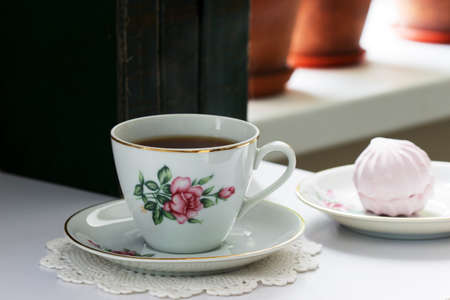 Tea in a vintage cup, marshmallows on a vintage saucer and old books on a light background. Selective focus.