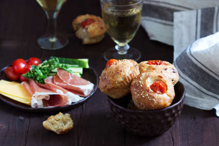 Muffins with cheese, cottage cheese and tomatoes, vegetables and cheese served with wine. Selective focus.