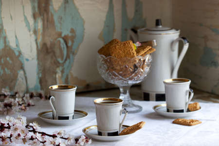 Coffee served with shortbread cookies and sweets on the background of flowering branches and an old cupboard. Rustic style, selective focus.