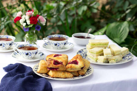 Afternoon tea in the garden with scones, strawberry jam, finger sandwiches with cucumber and egg salad on a light background. Selective focus. Archivio Fotografico