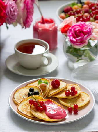 Curd pancakes with berry curd served with tea on a table decorated with bouquets of roses.