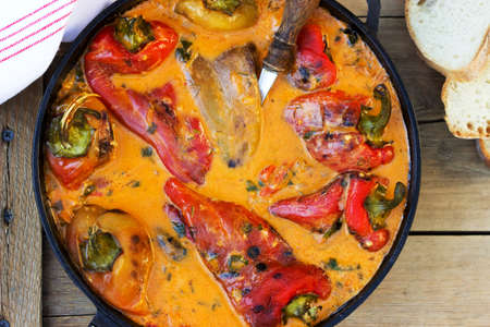 Sweet peppers in tomato and sour cream sauce, a traditional dish in some European countries. Rustic style.