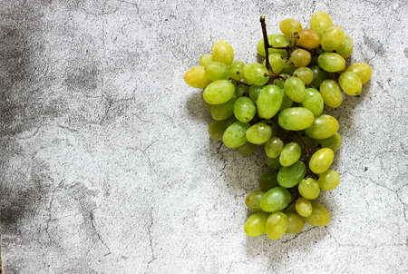 Amber bunch of grapes on a gray concrete background.