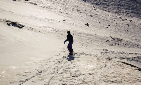 Snowboarder freerider. Snowboarder man holding snowboard in the air jumping with mountains on background