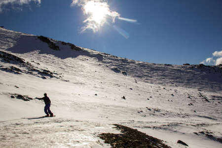 Snowboarder is riding with snowboard from powder snow hill in Cerro Catedral - Bariloche