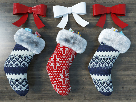 Beautiful red and blue Christmas socks with ribbons on wooden background