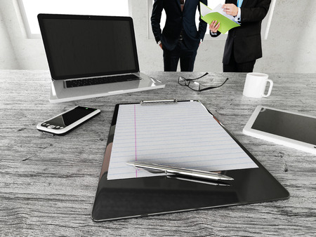 Business meeting in a beautiful office space including desk with laptop, tablet, cellphone, charts and eyeglasses Stock Photo