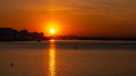 Bel tramonto sul grande fiume. Grande città e ponte sullo sfondo. Copyspace per il testo.