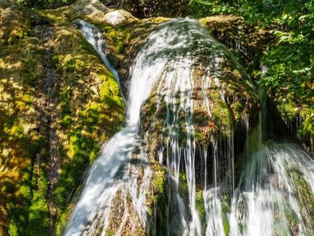Small waterfall on the river in the mountains. Closeup view of falling water down on the stones. 版權商用圖片