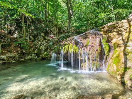 Small waterfall on the river in the mountains. Deep forest on the shores of river with stones and rocks. 版權商用圖片