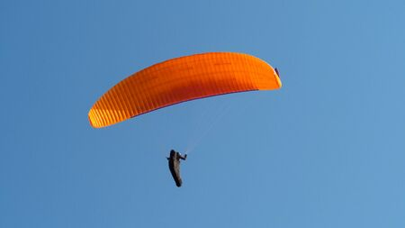 Paraglider is flying in the blue sky. Copyspace for text.