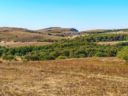 Pasto de montaña en día soleado de otoño. Hermosa vista de la meseta de yaila en las montañas de Crimea con hierba amarilla y cielo azul de fondo. Foto de archivo