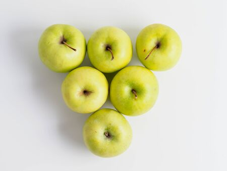 Top view of organic green apples isolated on white background.