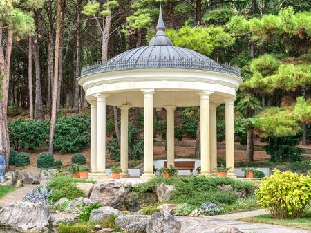 Gazebo in antique style in park of Partenit. Beautiful summerhouse near the pond with subtropical plants on the background. Archivio Fotografico