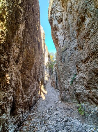 Pass in the canyon in Crimean mountains. Small gorge near Sudak on the top of mountain. Blue sky on the background.