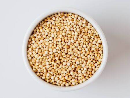 Quinoa seeds isolated on white background. Natural product in the plate with copyspace for text.