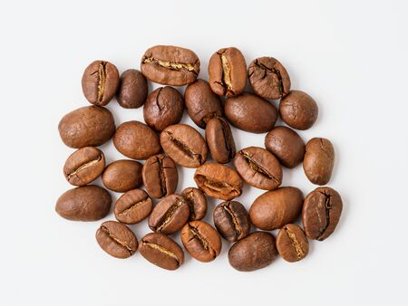 Roasted coffee beans isolated on white background. Copyspace for text.
