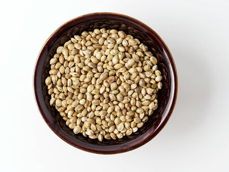 Seeds of hemp in the plate, isolated on white background. Copyspace for text and top view