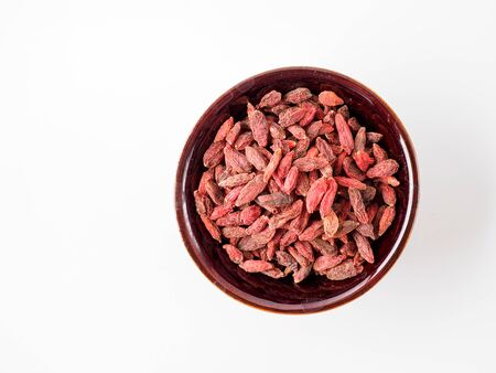 Goji berry isolated on white background in the plate. Copyspace for text.