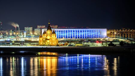 Winter view of soccer stadium in Nizhny Novgorod. Big orthodox cathedral in front of football arena.