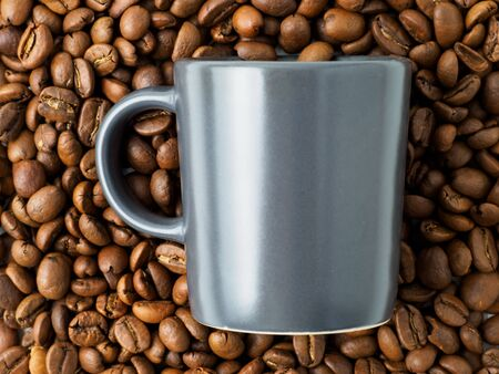 Coffee cup with beans on the background. Carpet of beans and blue cup.