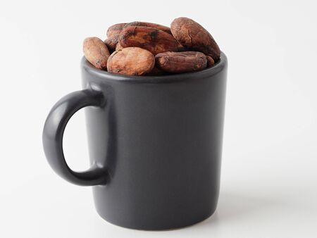 Cocoa beans isolated on white background. Cup for cocoa with whole beans and copyspace for text. Stok Fotoğraf