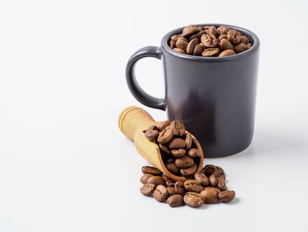 Roasted coffee beans in the cup. Isolated on white background with copyspace for text.