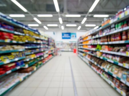 Abstract blurred supermarket aisle with colorful shelves and unrecognizable customers as background Stok Fotoğraf