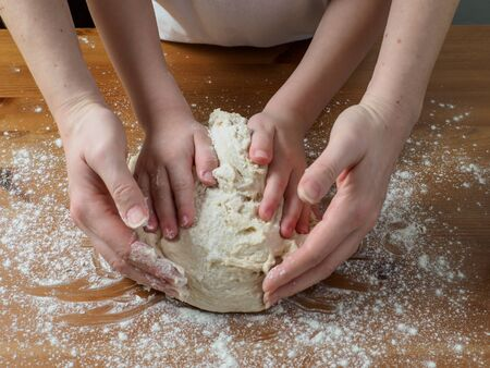 Woman and kid hands kneading dough for bread. Wooden table with white wheat flour on it.