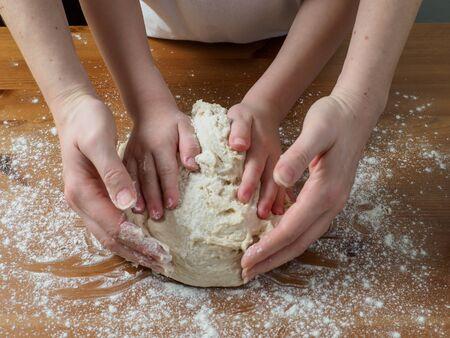 Mains de femme et d'enfant pétrissant la pâte pour le pain. Table en bois avec de la farine de blé blanche dessus.