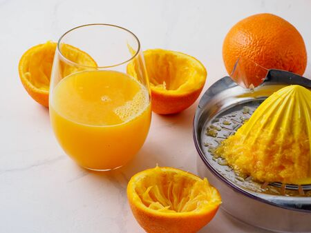 Manual juicer with cup of juice on white background.