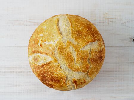 Loaf of bread on wooden background. Top view of natural domestic bakery.