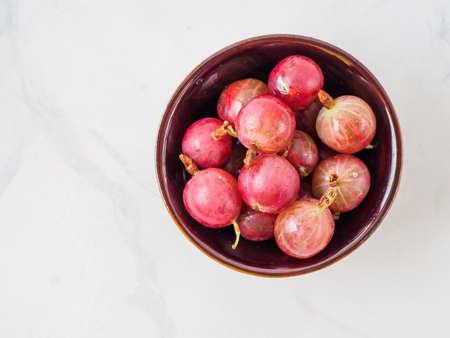 Bowl with fresh gooseberry on white wooden background. 版權商用圖片