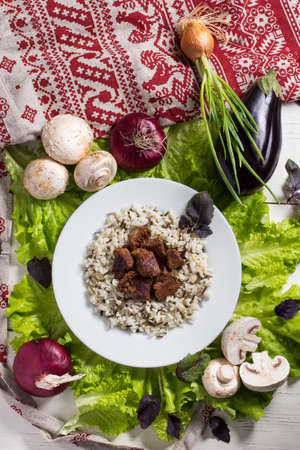 traditional pattern: still life - pork pieces with a garnish from brown rice Stock Photo